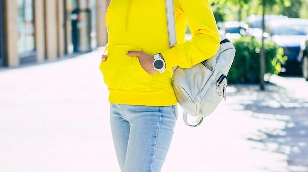Jasna bluza z kapturem. dziewczyna ze smartwatchem i srebrnym nowoczesnym plecakiem, trzymająca ręce w kieszeniach żółtej bluzy.