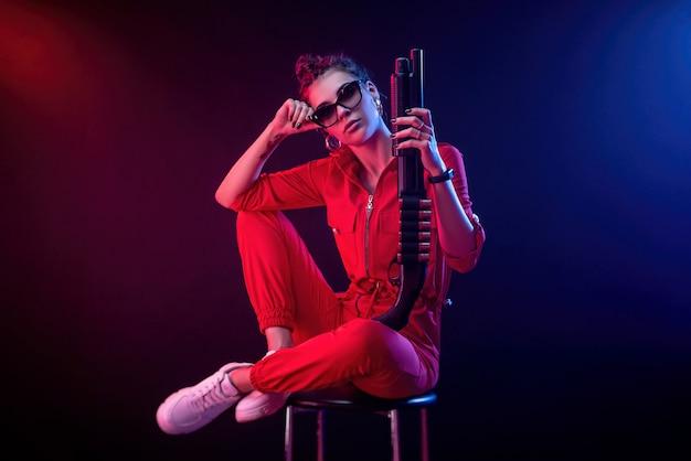 Jasna brunetka w czerwonym kombinezonie ze strzelbą na ciemnym tle w neonowym świetle