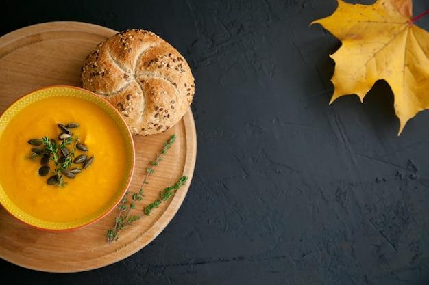 Jasna domowa zupa dyniowa z serem, podawana z pestkami, ziołami i bułką, na czarnym tle. widok z góry, miejsce na kopię.