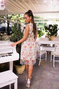 Jasna dziewczyna w kolorowej letniej sukience stojącej w pobliżu fortepianu, fryzura z ogonem, obcasy, moda, plener, impreza, wydarzenie, idealne ciało, niesamowity wygląd, makijaż, plecy