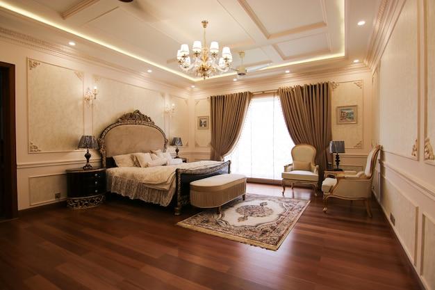 Jasna i przytulna luksusowa sypialnia o klasycznym designie, dużym oknie i parapecie z miękkimi siedziskami i poduszką