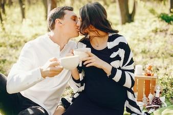 Jasna i szczęśliwa kobieta w ciąży siedzi w parku z mężem i picia herbaty