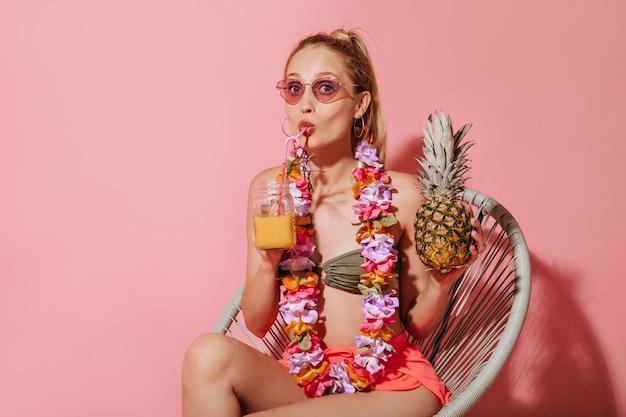 Jasna kobieta w stylowych okularach przeciwsłonecznych, kolczykach, fajnym kostiumie kąpielowym i naszyjniku z kwiatów pijąca sok pomarańczowy i trzymająca ananasa na różowej ścianie