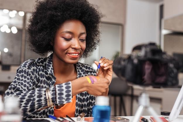 Jasna kolekcja. niesamowita kobieta z kręconymi włosami, która wygląda na zaangażowaną w przymierzanie nowej kolekcji kolorów