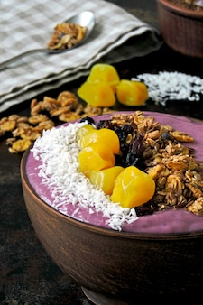 Jasna kolorowa miska acai z muesli i suszonymi owocami.
