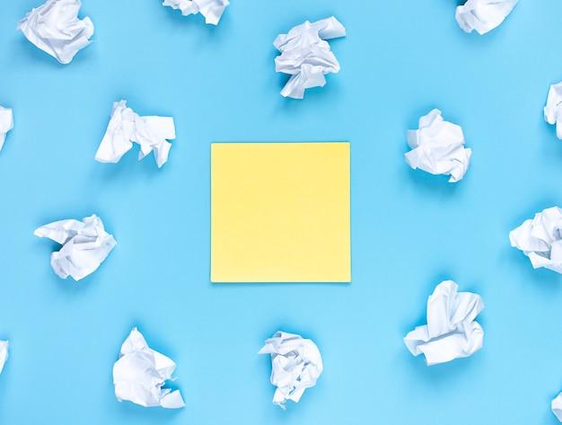 Jasna koncepcja kreatywności po wyjęciu z pudełka, żółta naklejka i białe pomięte papiery, układanie na płasko, miejsce na kopię