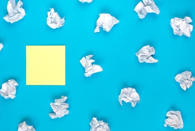 Jasna koncepcja kreatywności pomysłu, żółta naklejka i białe pomięte papiery, leżanka płaska, miejsce na kopię
