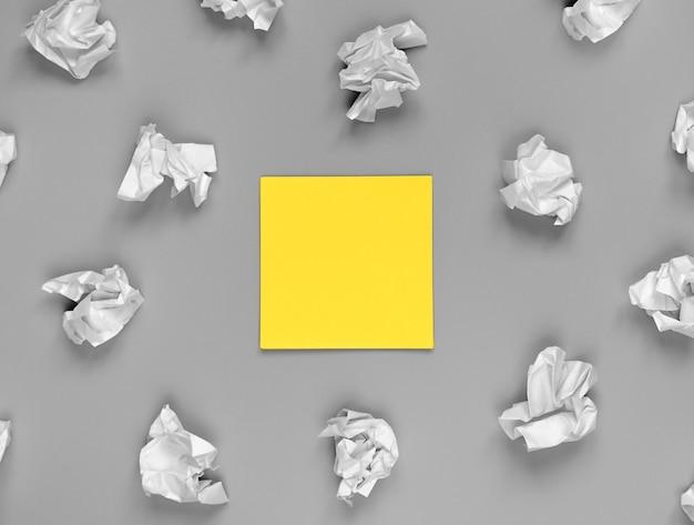 Jasna koncepcja kreatywności, żółta naklejka i pogniecione papiery. tło w kolorze roku
