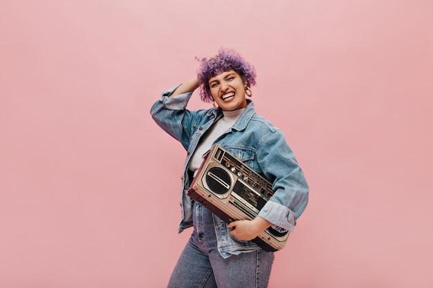 Jasna krótkowłosa kobieta w masywnych okrągłych kolczykach i szerokiej marynarce trzyma magnetofon w rzece i się śmieje.