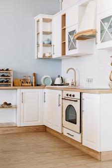 Jasna kuchnia w stylu skandynawskim z naczyniami i akcesoriami kuchennymi na stole.