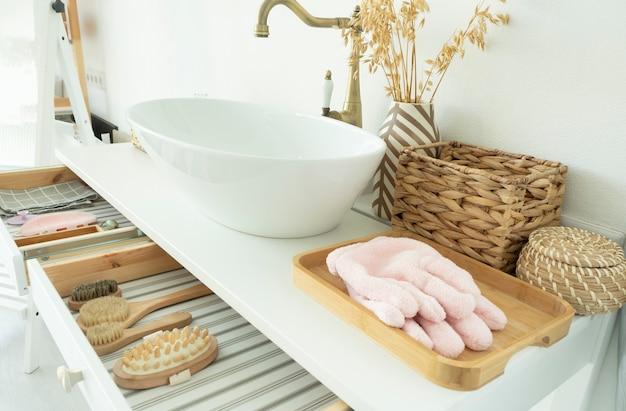 Jasna łazienka. wysuwane szuflady z masażerami i szczotkami. wiklinowe kosze i zlew.
