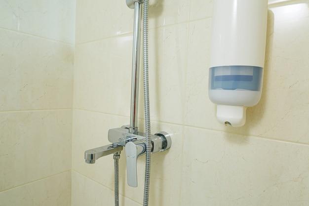 Jasna łazienka z prysznicem, słuchawką prysznicową, jasna płytka
