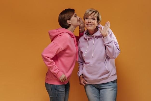 Jasna młoda dziewczyna z krótkimi włosami brunetki w różowej bluzie z kapturem mówi sekret starszej pani w liliowej stylowej bluzie z kapturem na na białym tle.