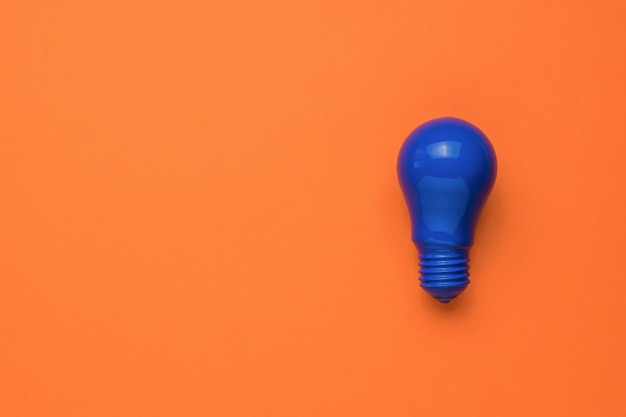 Jasna niebieska żarówka na pomarańczowym tle. minimalizm. leżał płasko.