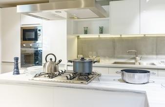 Jasna, nowoczesna kuchnia z urządzeniami ze stali nierdzewnej. Projektowanie wnętrz.