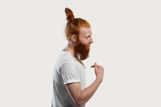 Jasna osoba w białej koszulce z rudymi włosami i dużą brodą wskazująca na siebie