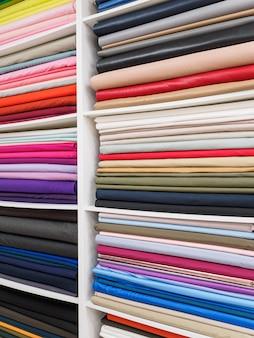 Jasna paleta zbliżenie kolorowych dzianin. próbki jasnych tkanin na półkach w sklepie.
