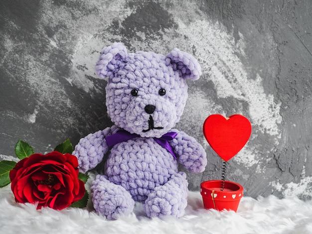 Jasna pluszowa zabawka i kwitnąca czerwona róża