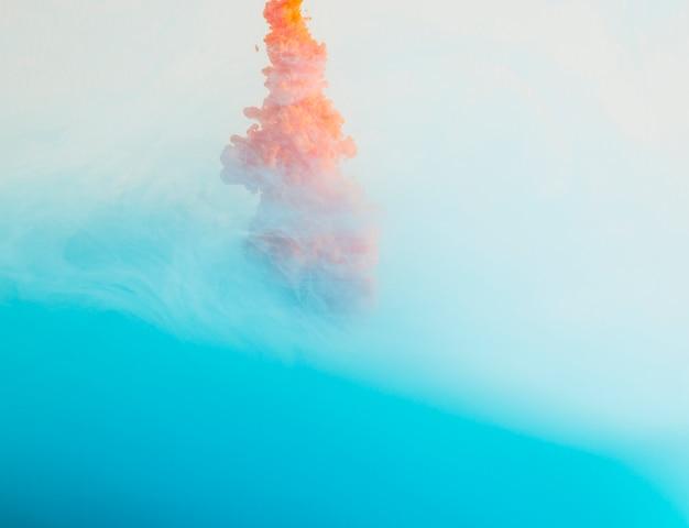 Jasna pomarańczowa kropla w niebieskiej mgle