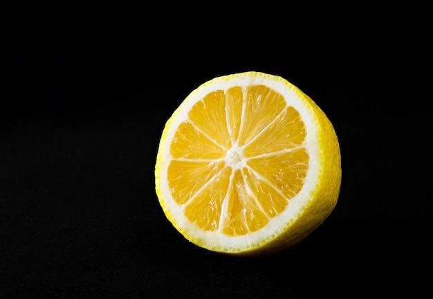 Jasna soczysta żółta cytryna na czarnym tle
