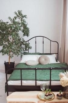 Jasna sypialnia z łóżkiem z czarną metalową ramą i drzewkiem do domu
