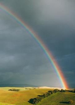 Jasna tęcza i zielone wzgórza na tle ciemnego nieba pochmurnego