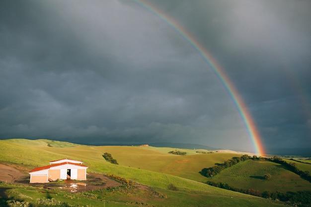 Jasna tęcza i zielone wzgórza z małym domkiem na ciemnym tle pochmurnego nieba