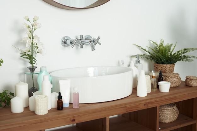 Jasna umywalka łazienkowa z tubkami kremu, słoiczkami serum do twarzy i czystymi ręcznikami. koncepcja pielęgnacji skóry, codziennego mycia i czystości.
