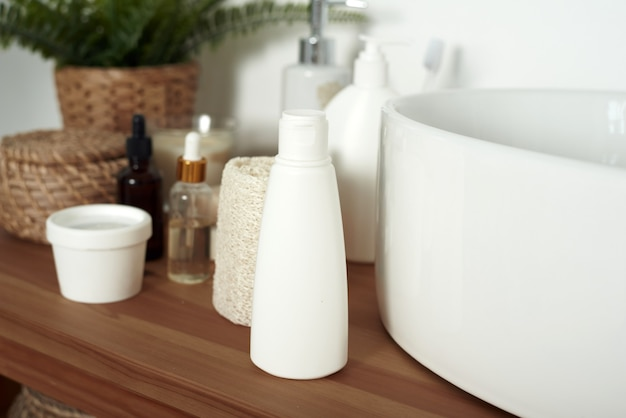 Jasna umywalka łazienkowa z tubkami kremu, słoiczkami serum do twarzy i czystymi ręcznikami.