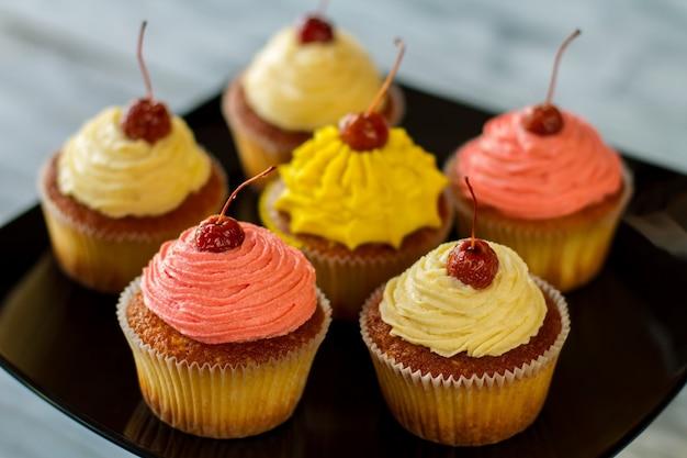 Jasne babeczki z wiśniowymi deserami na czarnym talerzu zaskoczą twoich gości domowym ciastem z polewą