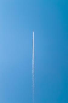 Jasne błękitne niebo i pionowy ślad samolotu.
