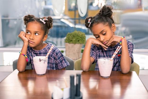 Jasne bransoletki. śliczne modne siostry noszące ładne, jasne bransoletki nudzą się siedząc w stołówce