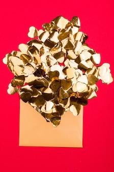 Jasne czerwone tło ze złotymi sercami, świąteczny pojemnik, święta wszystkich miłośników. miejsce na napis.