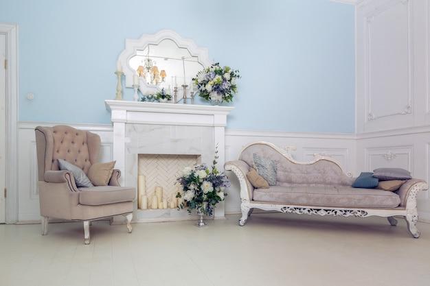 Jasne, czyste stylowe wnętrze sypialni i salonu z dużym panoramicznym oknem. piękne bogate antyczne meble. łóżko z baldachimem, lustro i sofa.