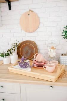 Jasne drewniane wnętrze kuchni. piękny wystrój kuchni. bladoróżowe talerze talerze kubki