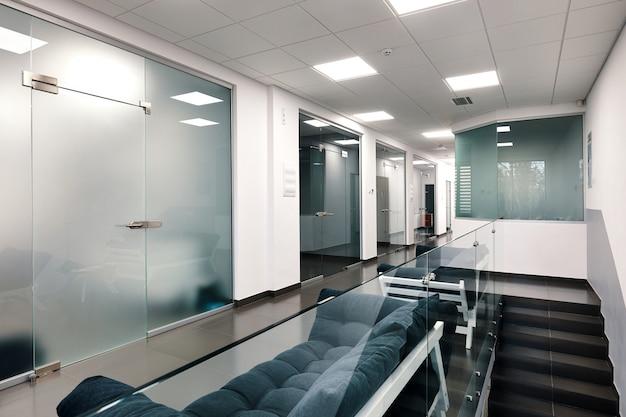 Jasne duże nowoczesne wnętrze biura ze szklanymi drzwiami