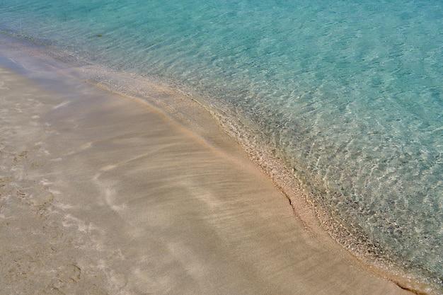Jasne fale i kolorowy piasek na tropikalnej, piaszczystej plaży w grecji na krecie.