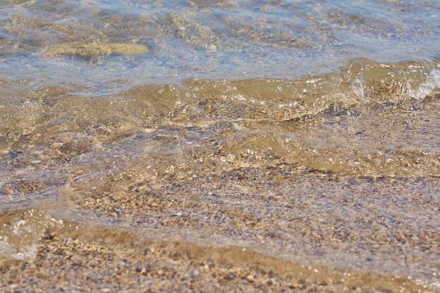 Jasne fale na tropikalnej, piaszczystej plaży na krecie w grecji.
