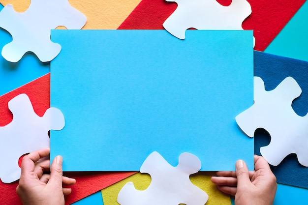 Jasne geometryczne tło, wielokolorowy filc i białe puzzle. ręce trzymaj niebieską papierową stronę z miejscem na tekst, umieść na swoim podpisie.