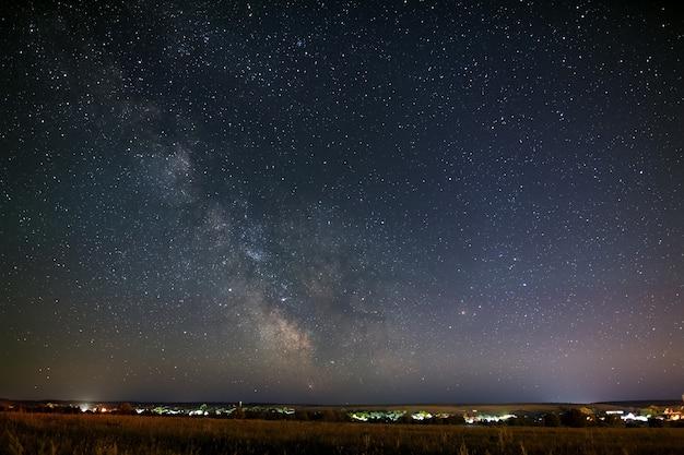 Jasne gwiazdy będące częścią drogi mlecznej na nocnym niebie. widok na gwiaździstą przestrzeń w tle świateł na horyzoncie.