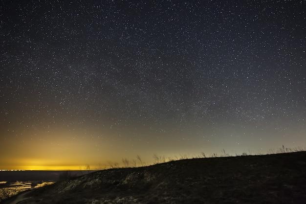 Jasne gwiazdy na nocnym niebie na tle wzgórz. krajobraz z długą ekspozycją.