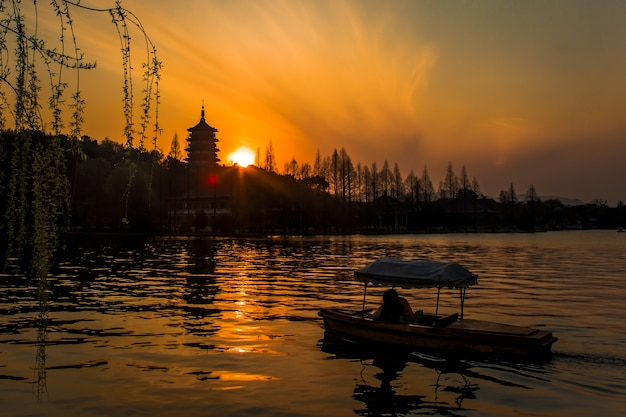Jasne, hipnotyzujące słońce zachodzące nad jeziorem zachodnim w hangzhou w chinach