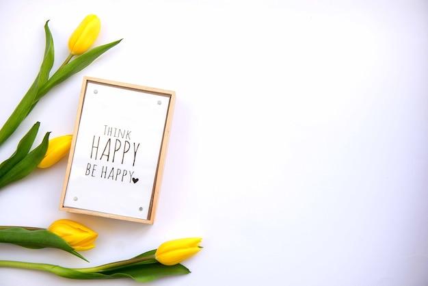 Jasne i kolorowe letnie tło płaskie leżało z żółtymi kwiatami tulipanów i słowami motywacyjnymi