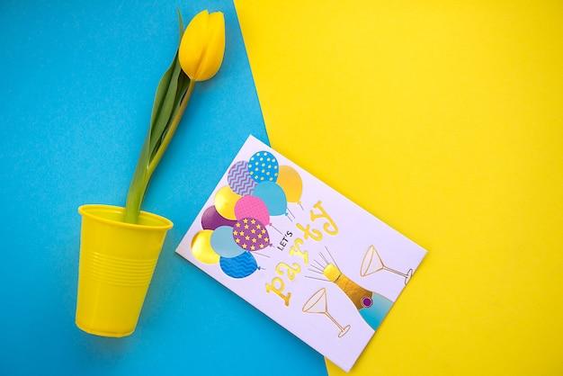 Jasne i kolorowe letnie tło płaskie leżało z żółtymi tulipanami na niebiesko
