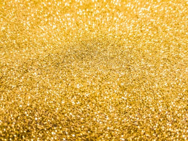Jasne i musujące tło bokeh. żółte złoto - niewyraźne oświetlenie z tekstury brokatu.