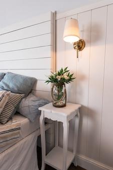 Jasne i wygodne wnętrza sypialni. styl skandynawski. kwiaty na stoliku nocnym. poduszka na łóżko. wnętrze pokoju. płonąca mała lampka nad stołem.