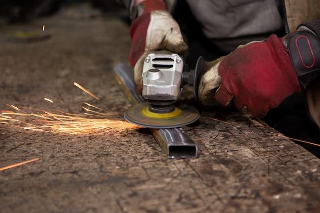 Jasne iskry lecą, gdy robotnik szlifuje metalową konstrukcję.