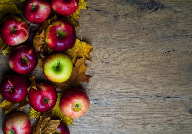 Jasne jesienne jabłka z żółtymi liśćmi na drewnianym stole, miejsce na tekst, jesień tło. zdjęcie wysokiej jakości