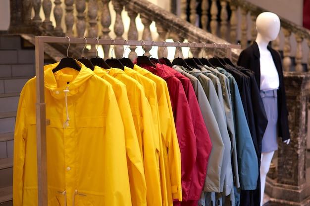 Jasne kolorowe jesienne płaszcze przeciwdeszczowe wiszące w sklepie z modą.
