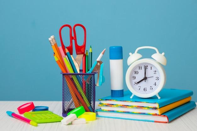 Jasne, kolorowe książki, budzik i kolorowe kredki na jasnym tle. powrót do szkoły.